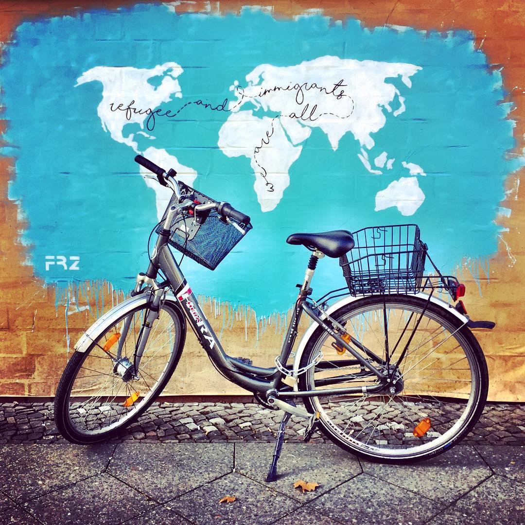 """#paracegover Descrição para deficientes visuais: a imagem mostra uma bicicleta estacionada na frente de um mapa desenhado na parede. O mapa-mundi branco sobre o fundo azul traz a seguinte frase escrita em letra cursiva atravessando os continentes: """"we are all immigrants and refugee"""". — at URBAN NATION."""