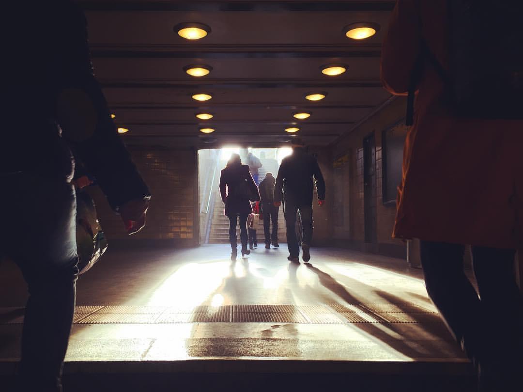 #paracegover Descrição para deficientes visuais: a imagem mostra uma cena escura (o corredor de saída da estação de metrô). Ao fundo, a escada com a luz do dia entrando. A silhueta das pessoas deu um tom de mistério... — at Märkisches Museum (Berlin U-Bahn).
