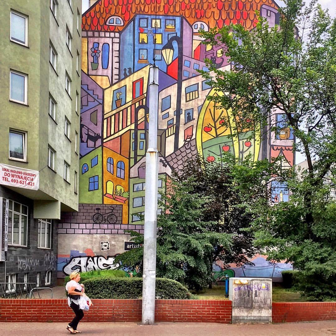 #paracegover Descrição para deficientes visuais: a imagem mostra uma mulher caminhando apressada por uma calçada em frente a um jardim. Ao fundo, uma parede cega decorada com um mural coloridíssimo, retratando um conjunto de prédios em estruturas geométricas.