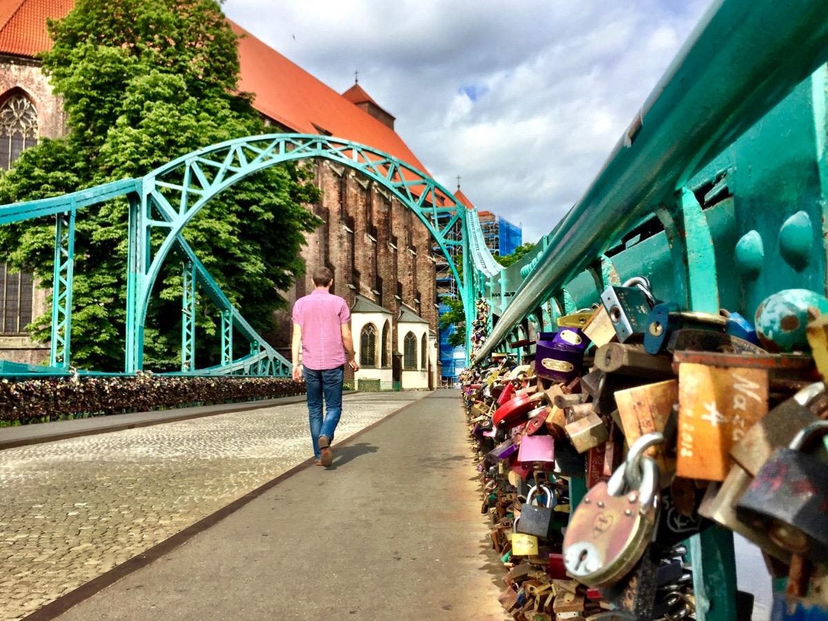 A imagem mostra uma ponte de ferro pintada de azul turquesa cujas grades laterais estão cheias de cadeados. Um homem de jeans e camisa rosa é visto de costas passando por ela.