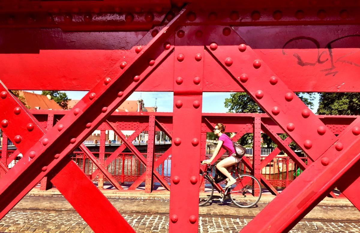 A imagem mostra uma ponte de ferro vermelha enquanto uma ciclista vestida de rosa faz a travessia.