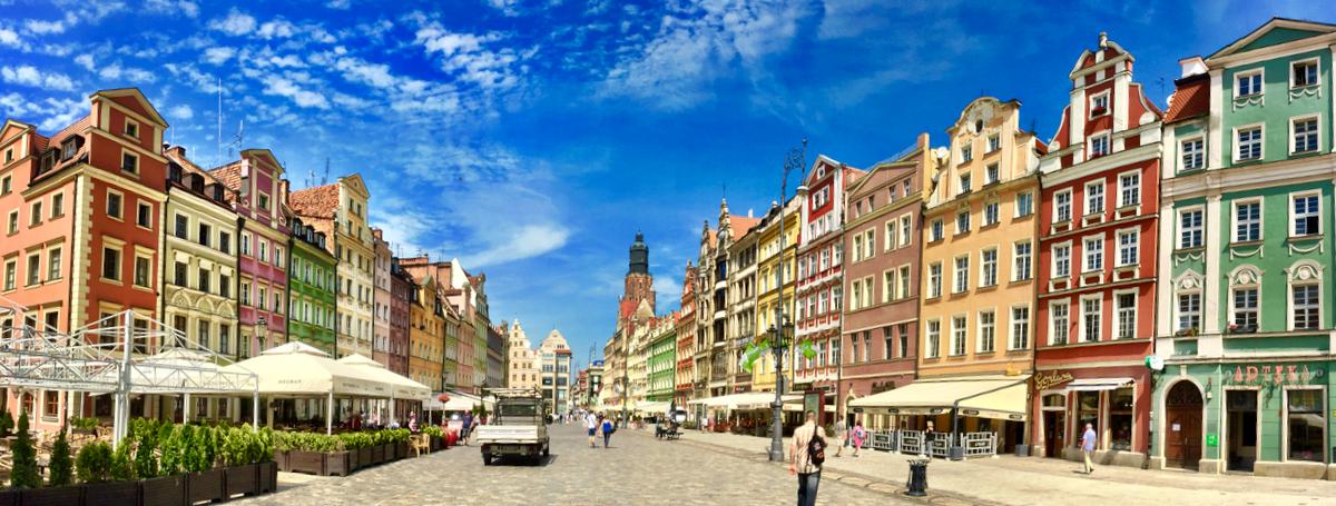 A imagem mostra uma rua larga com um casario colorido em ambos os lados. O céu está bem azul.