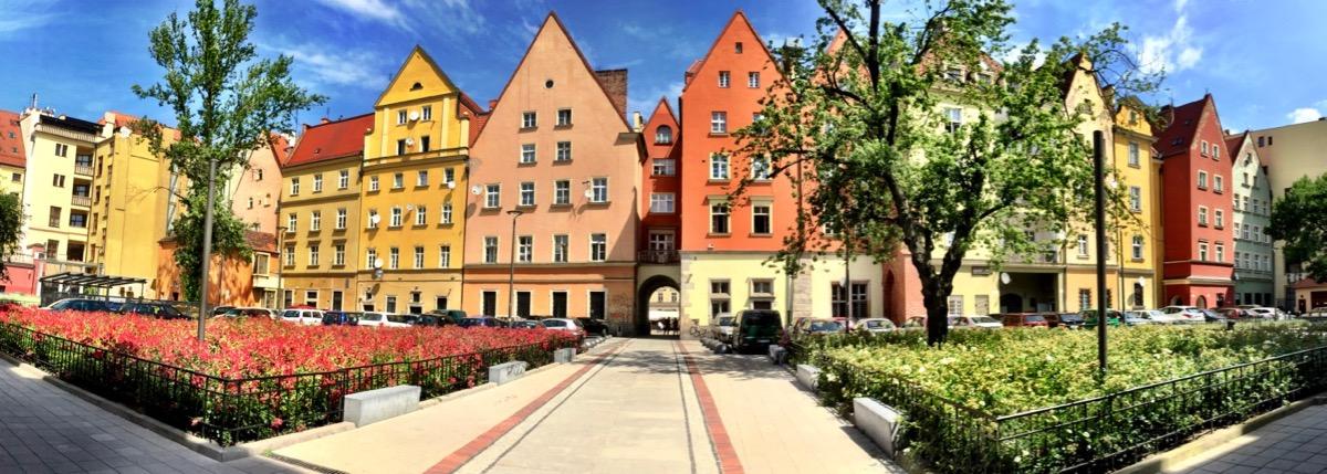 A imagem mostra uma visão panorâmica do casario de um pátio interno. As casas têm telhados triangulares e são pintadas de cores quentes.