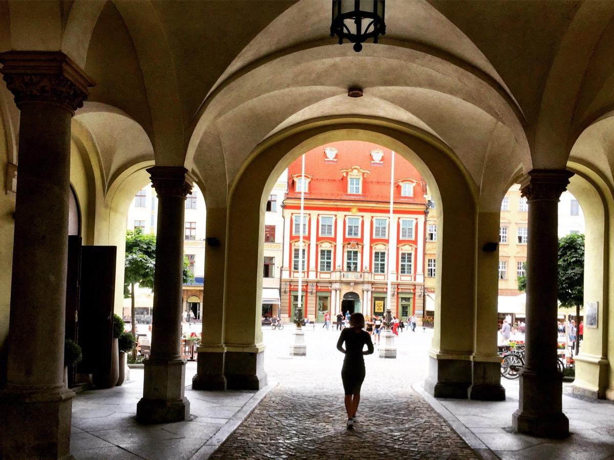 A imagem mostra um portal em forma de arco por onde se vê a silhueta de uma mulher passando. Ao fundo, um prédio vermelho e laranja na praça principal.
