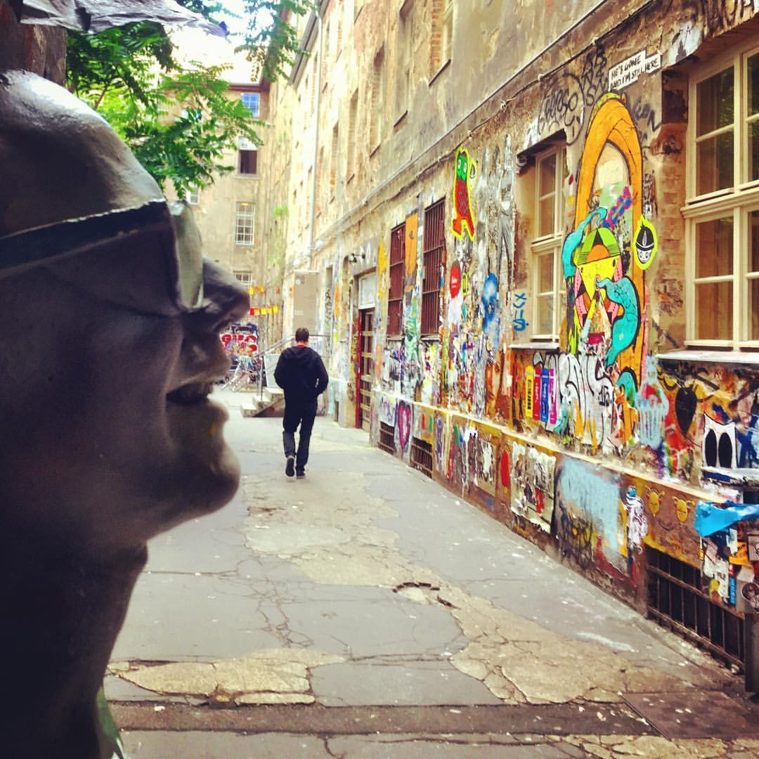 #paracegover Descrição para deficientes visuais: a imagem mostra o pátio interno de um prédio com as paredes grafitadas. Uma escultura de um homem sorridente usando óculos de sol aparece de perfil em primeiro plano. Na altura da boca, pode-se ver a silhueta de uma pessoa que passa, criando um jogo visual. — at Café Cinema.