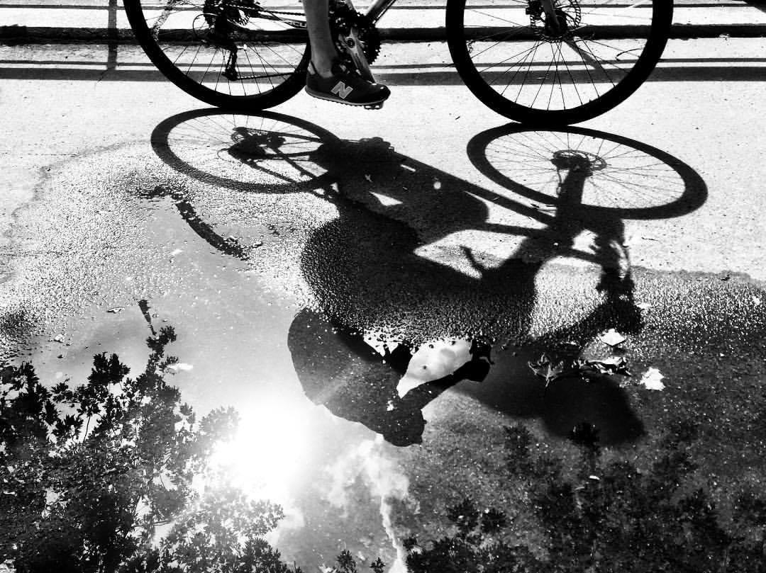#paracegover Descrição para deficientes visuais: a imagem mostra o reflexo em uma poça d'água da silhueta de uma bicicleta que passa (aparecem apenas as rodas e os pés do ciclista). A foto está em preto e branco para melhorar o contraste. — at Märkisches Ufer.