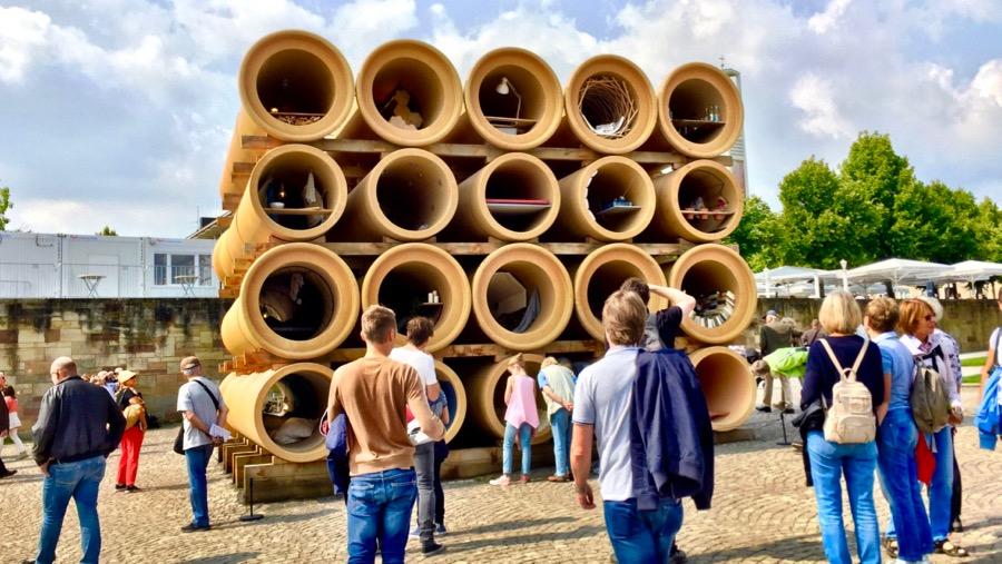 Canos gigantes empilhados vistos de frente. Há muitas pessoas observando.