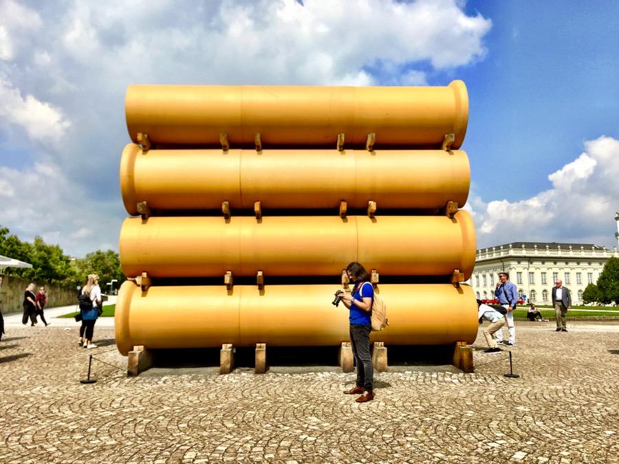 A imagem mostra canos gigantes empilhados vistos pela lateral.