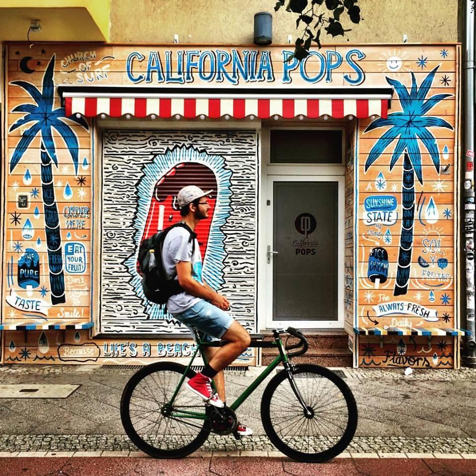 #paracegover Descrição para deficientes visuais: a imagem mostra um rapaz passando de bicicleta na ciclovia bem em frente a uma sorveteria, que está fechada no momento. A fachada é toda decorada com desenhos e dizeres que remetem ao verão. Há um coqueiro azul desenhado em cada lado da fachada. — at California Pops - Prenzlauer Berg.