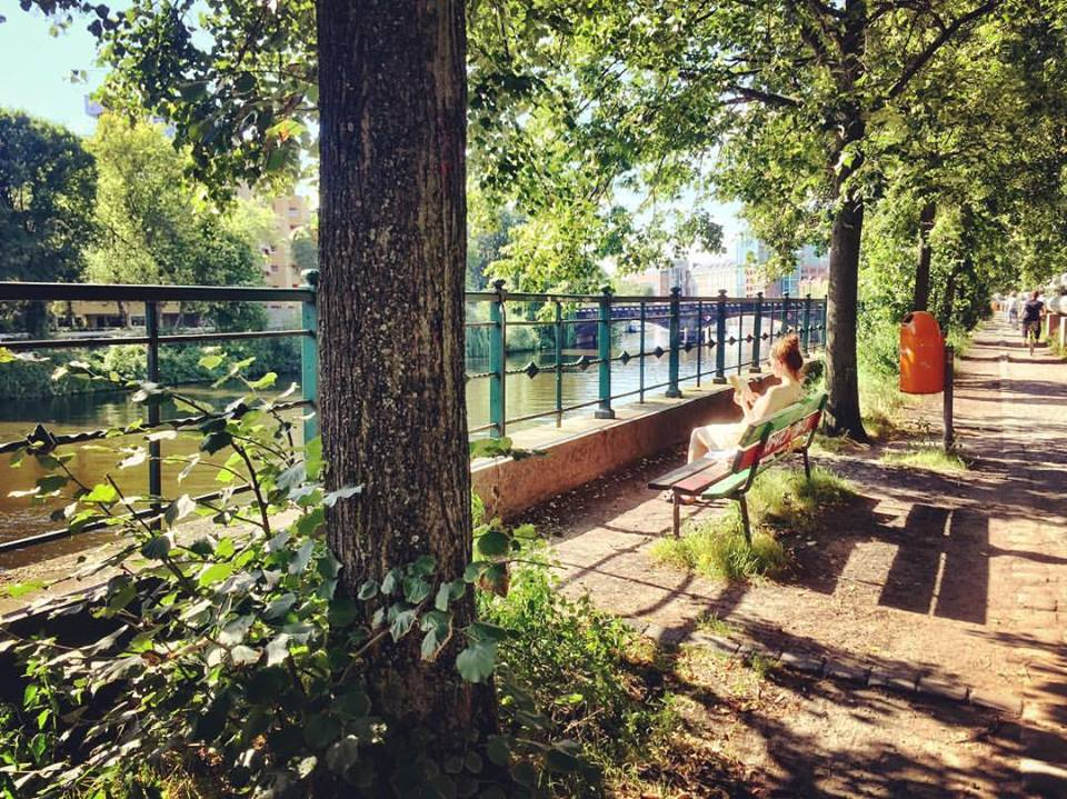 #paracegover Descrição para deficientes visuais: a imagem mostra uma moça sentada num banco lendo, à sombra das árvores, às margens do rio Spree. Ao longe é possível ver a ponte de ferro de Moabit. O dia está perfeito. — at Helgoländer Ufer.