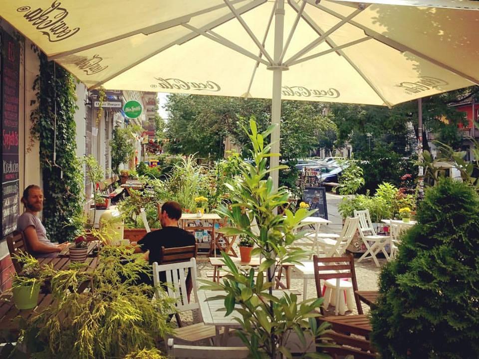 #paracegover Descrição para deficientes visuais: a imagem mostra as mesas de um café na calçada larga e arborizada. Um ombrelone protege os frequentadores do sol. É a paz materializada em paisagem urbana. — at Café Entweder Oder.