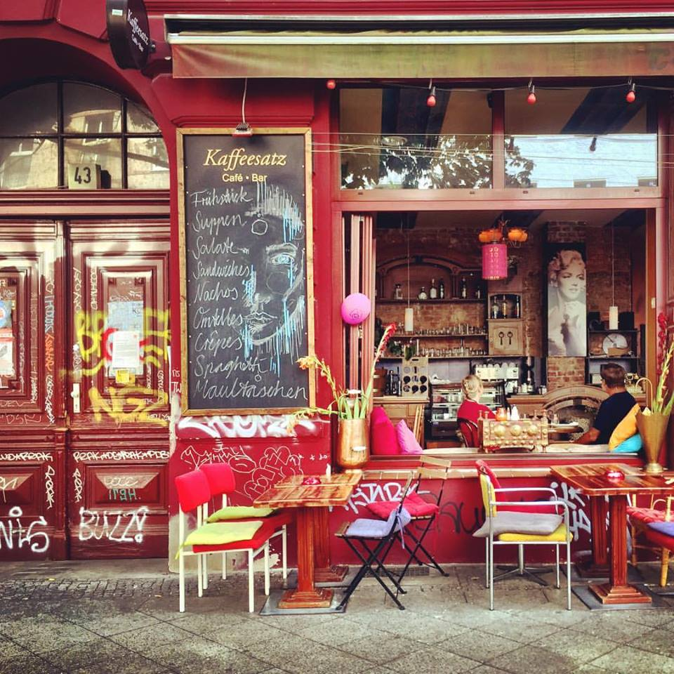 #paracegover Descrição para deficientes visuais: a imagem mostra a fachada de um belíssimo café; as paredes são de um vermelho intenso e as almofadas das cadeiras na calçada e são pink, amarelo, verde-limão e lilás. Os vasos são cor de cobre. Pela janela pode-se ver dois clientes sentados do lado de dentro: um homem veste camiseta preta e uma mulher está de blusa vermelha. — at Kaffeesatz.