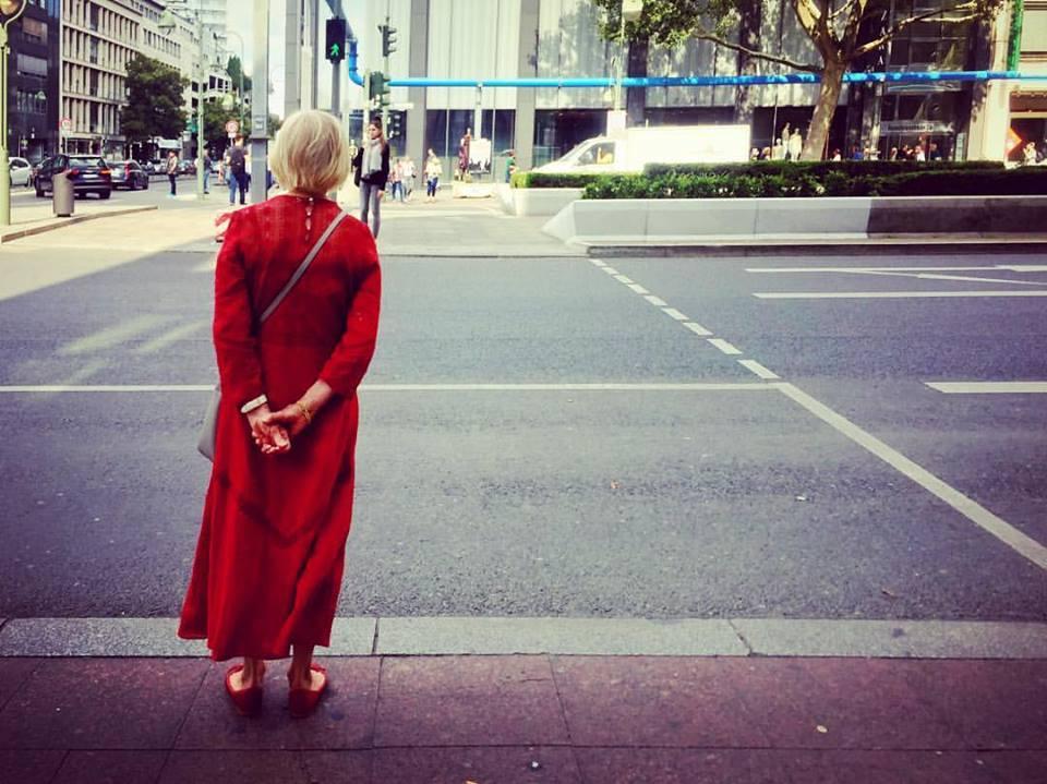 #paracegover Descrição para deficientes visuais: a imagem mostra uma mulher de cabelos brancos vestindo um longo vermelho esperando para atravessar uma avenida larga. Ela está de costas, comas mãos para trás. A rua está praticamente vazia, exceto por um furgão branco que passa do outro lado. — at Kurfürstendamm (Berlin U-Bahn).