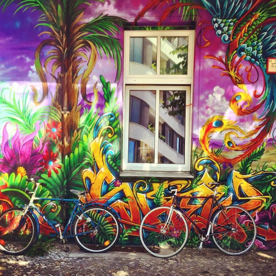 #paracegover Descrição para deficientes visuais: a imagem mostra duas bicicletas estacionadas sob uma janela instalada num prédio cujas paredes da fachada estão grafitadas de maneira espetacular. Cores quentes e intensas, parece que o desenho está vivo e fervendo! — at All Style Tattoo Berlin.