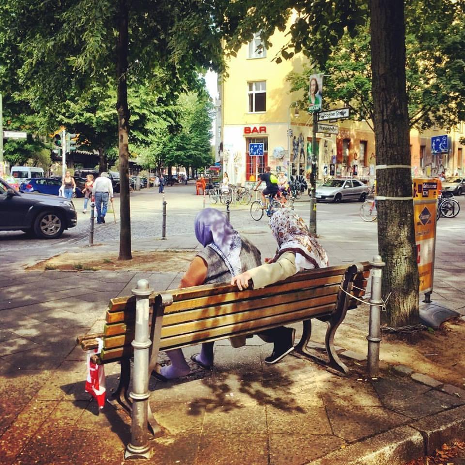 #paracegover Descrição para deficientes visuais: a imagem mostra duas mulheres muçulmanas sentadas num banco de praça observando o movimento. Elas estão de costas embaixo de uma árvore. Pessoas passam caminhando e de bicicleta. — at Estate Coffee.