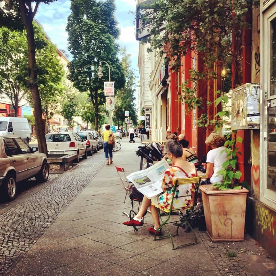 #paracegover Descrição para deficientes visuais: a imagem mostra pessoas num café em mesas na calçada lendo jornal. A rua é arborizada e as paredes do café são laranja escuro. — at Kaffeesatz.