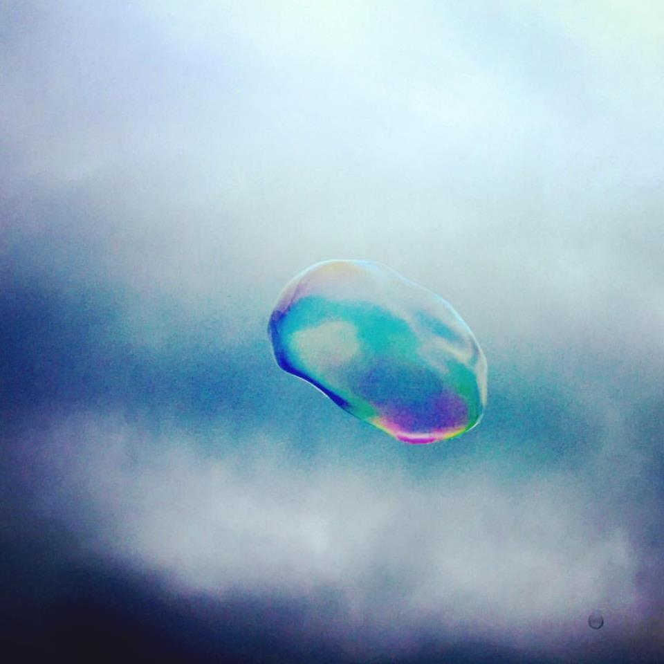 #paracegover Descrição para deficientes visuais: a imagem mostra uma bolha de sabão sob o céu nublado. O reflexo da pouca luz que incide sobre ela é furta-cor. — at Mauerpark.