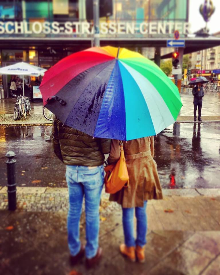 #paracegover Descrição para deficientes visuais: a imagem mosyra um casal de costas, esperando o sinal abrir para atravessar a rua. Eles estão protegidos por um enorme guarda-chuva com gomos coloridos. Chove. — at Schloßstraßen Center.