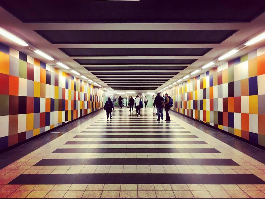 #paracegover Descrição para deficientes visuais: a imagem mostra um dos corredores de acesso da estação de metrô Gesundbrunnen. O caminho é lago e pode-se ver a silhueta de algumas pessoas caminhando ao fundo. As paredes laterais são decoradas com azulejos coloridos, numa paleta de cores quentes. — at Berlin-Gesundbrunnen station.