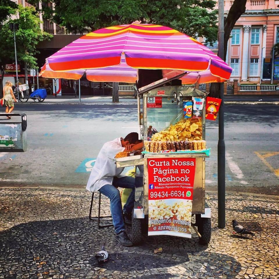 """#paracegover Descrição para deficientes visuais: a imagem mostra um carrinho de salgadinhos com uma sombrinha rosa. O atendente está visivelmente exausto e tira um cochilo. Uma placa vermelha, em destaque, convida: """"Curta nossa página no Facebook"""". — at Palácio das Artes."""