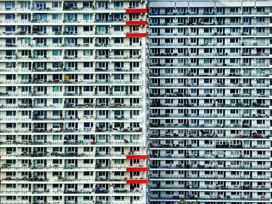 #paracegover Descrição para deficientes visuais: a imagem mostra a fachada de dois prédios enormes, com suas sacanas e janelas. A quantidade de habitações é tão grande que parece uma estampa miúda. Tudo é cinza, exceto alguns detalhes em vermelho. Impressionante. — at Berlin Mitte.