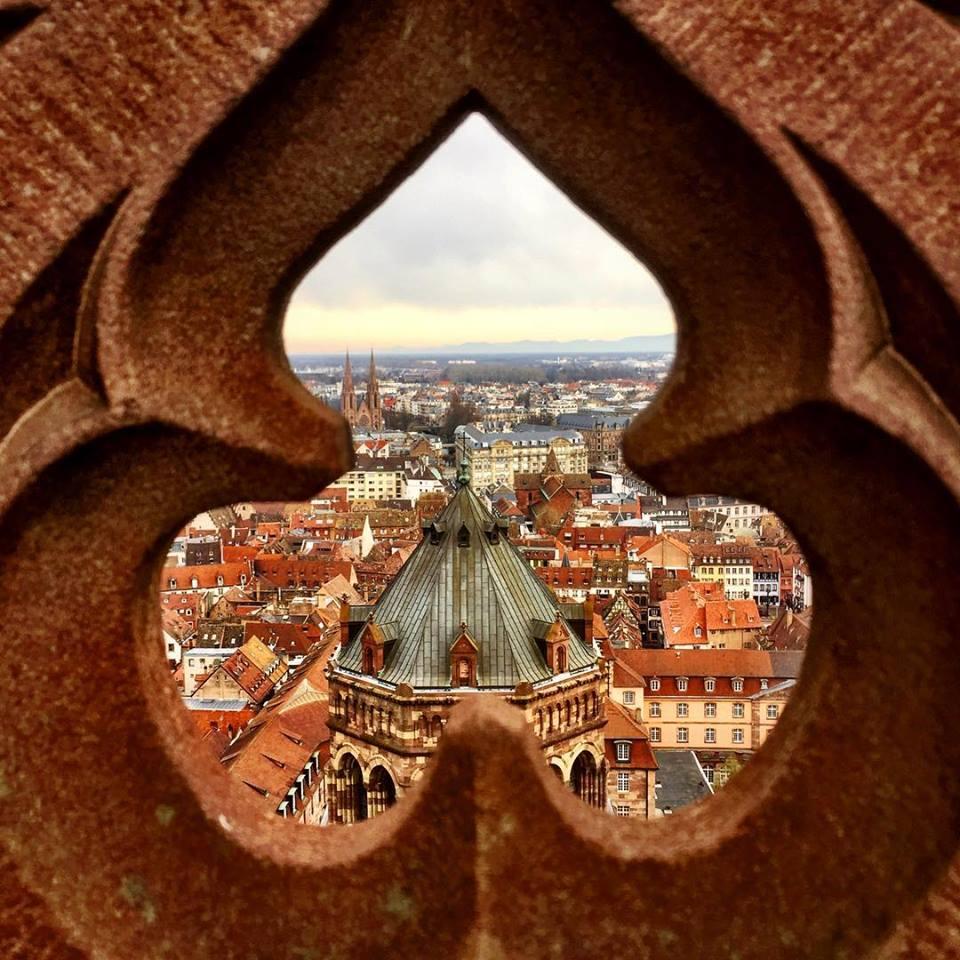 #paracegover Descrição para deficientes visuais: a imagem mostra uma parte da cidade de Strasburgo com seus telhados maravilhosamente inclinados através da fenda em forma de trevo da cerca vazada do pátio de observação.