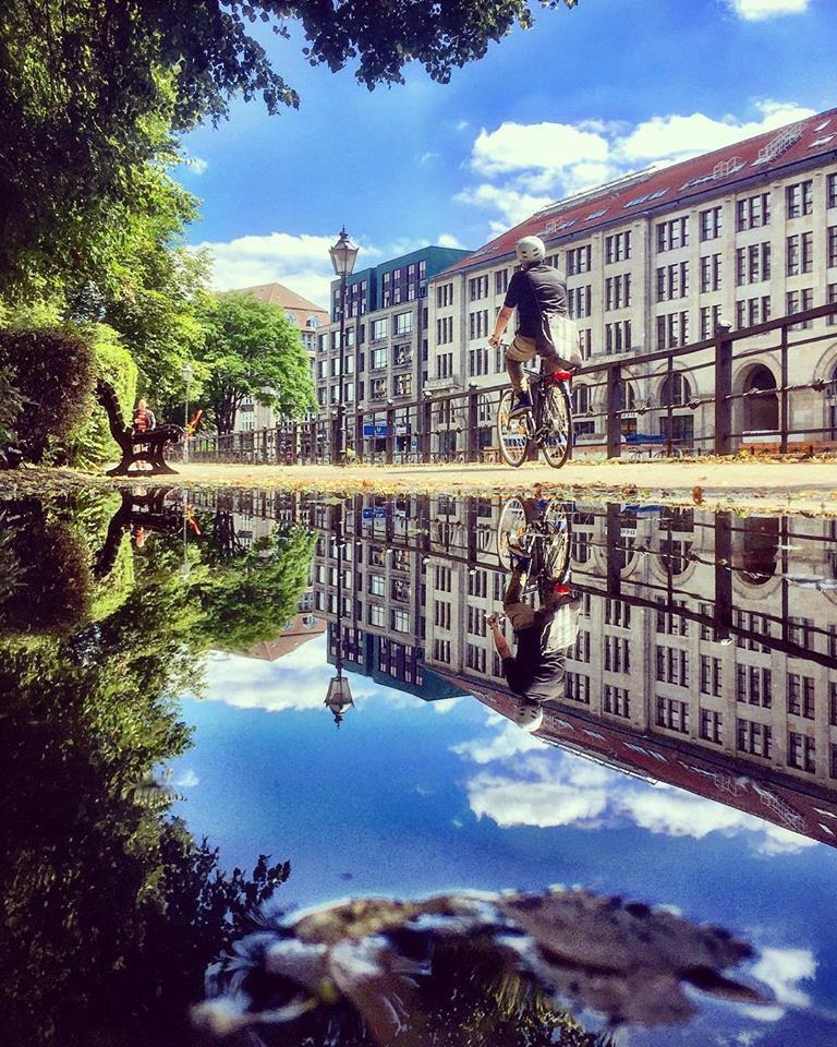 #paracegover Descrição para deficientes visuais: a imagem mostra um ciclista passando pela margem de um dos canais do rio Spree. Ao fundo, prédios e céu azul. A cena é refletida numa poça d'água. — at Spittelmarkt.