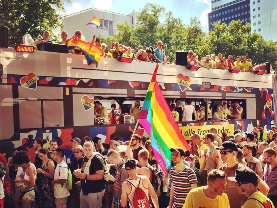 #paracegover Descrição para deficientes visuais: a imagem mostra o trio elétrico da empresa de transportes coletivos de Berlim no Christopher Street Day — a Parada Gay  — as pessoas estão por todos os lados, dançando e portando bandeiras com as cores do arco-íris. — at Nollendorfplatz.