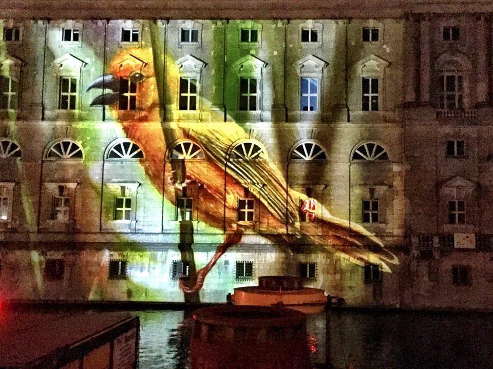 #paracegover Descrição para deficientes visuais: um passarinho colorido é projetado num prédio enorme onde funciona uma escola de música. — at Nikolaiviertel - Heart of Berlin.