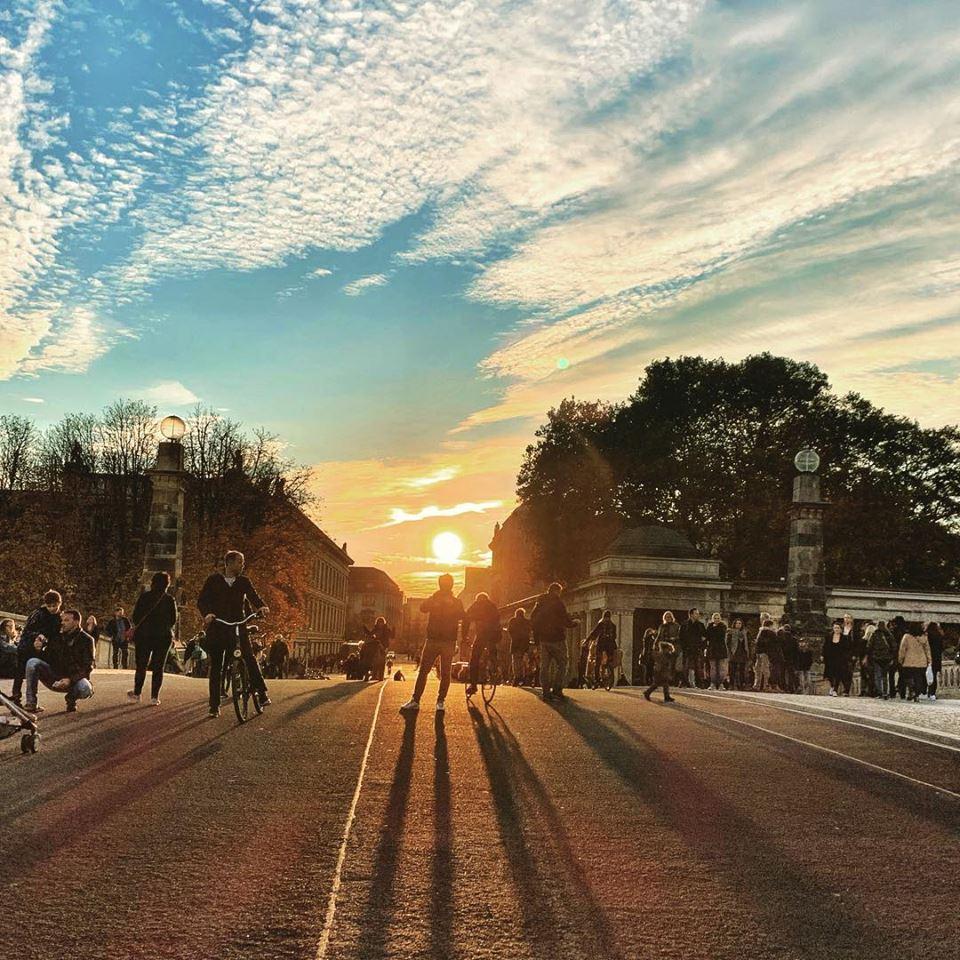 #paracegover Descrição para deficientes visuais: a imagem mostra pessoas em cima de uma ponte contra a luz do sol, que está se pondo. — at Friedrichsbrücke Berlin.
