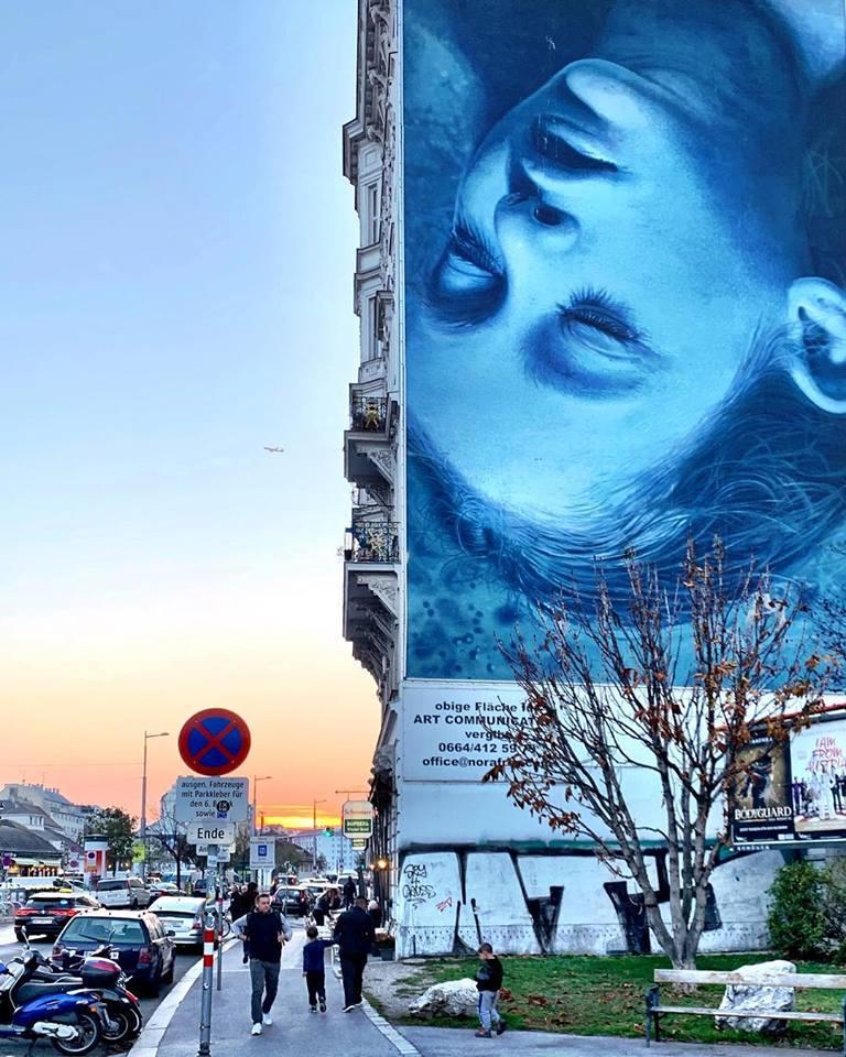 #paracegover Descrição para deficientes visuais: a imagem mostra um grafite gigante numa parede cega do lado direito, onde aparece a cabeça invertida de uma mulher, com fundo azul. Do lado esquerdo, um por-do-sol espetacular. Pessoas caminham na calçada. — at Naschmarkt.