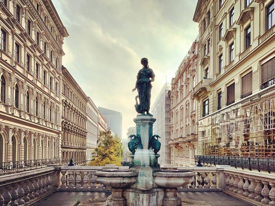 #paracegover Descrição para deficientes visuais: a imagem mostra uma estátua com chafariz, em primeiro plano. Ao fundo, prédios antigos à luz da manhã. — at Mumok, Museum of Modern Art, in Vienna.