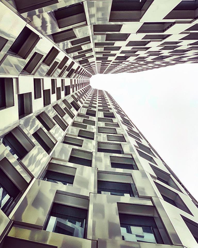 #paracegover Descrição para deficientes visuais: a imagem mostra o prédio de um hotel visto de baixo para cima. As linhas curvas e a fachada espelhada criam um efeito interessante. — at Motel One Berlin-Upper West.